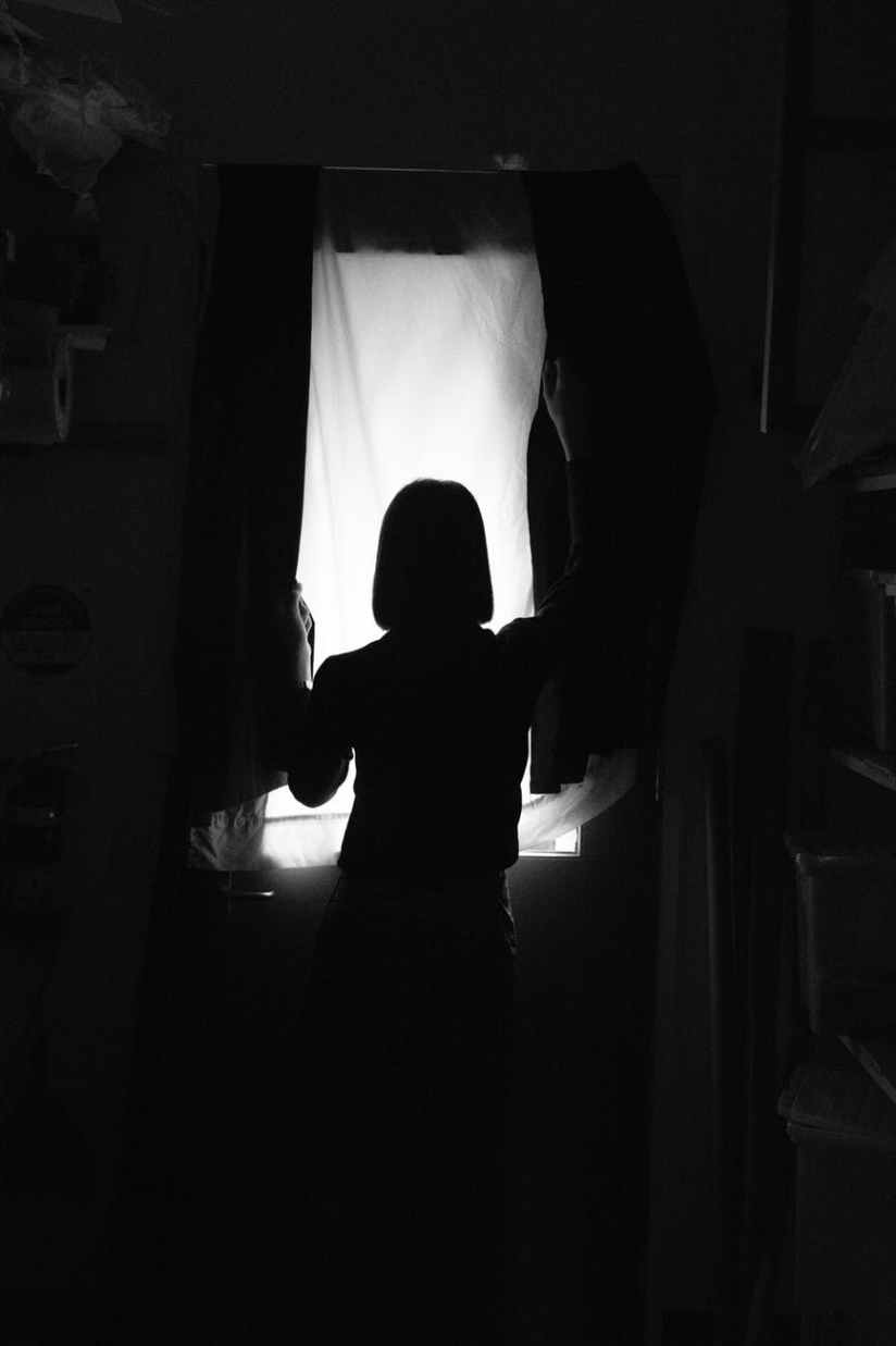 silhouette photo of person standing in front of window